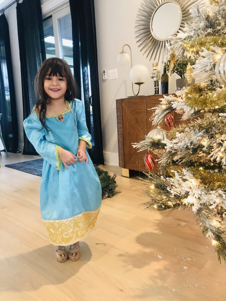 Little girl wearing Elsa dress standing next to gold Christmas tree.