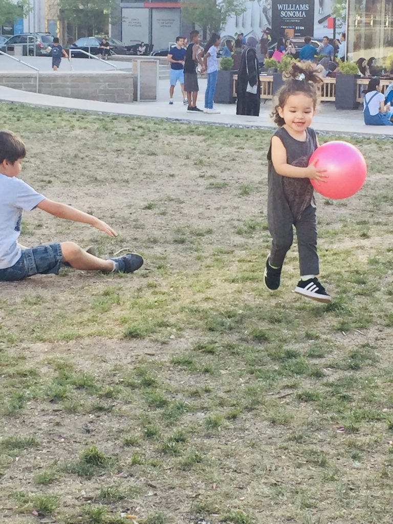 Little girl playing with red ball at the park.