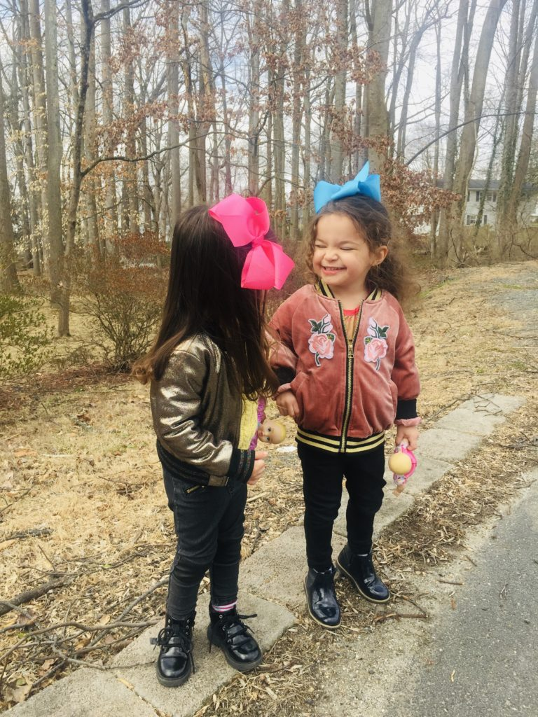 Fashionable twin toddlers playing outside with big bows in their hair and bomber jackets on.