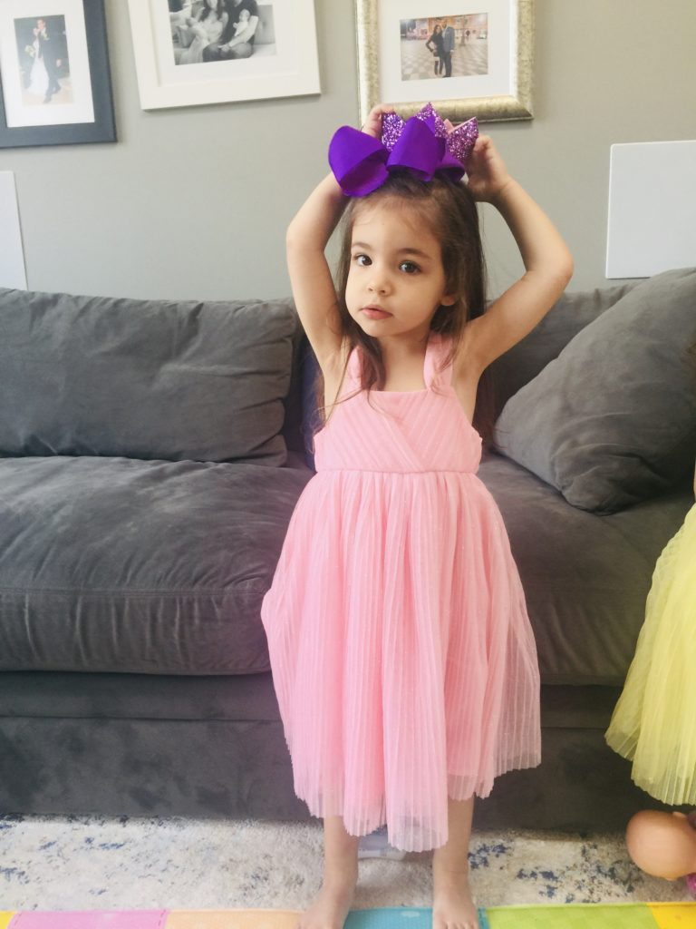 Little girl in pink dress with large purple bow in her hair.