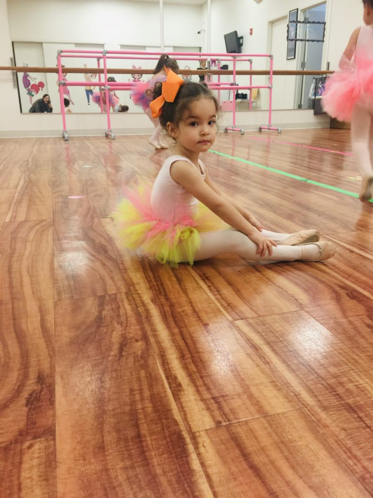 Little girl in ballet class wearing a tutu and a bow